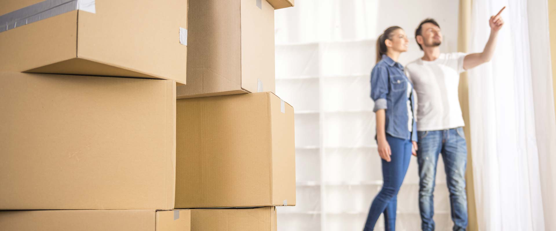 Moving boxes, and couple looking at new apartment